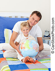 Blissful father and his child holding a terretrial globe