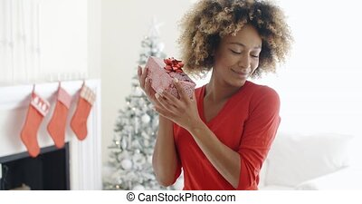 Blissful happy young woman holds a Christmas gift - Blissful...