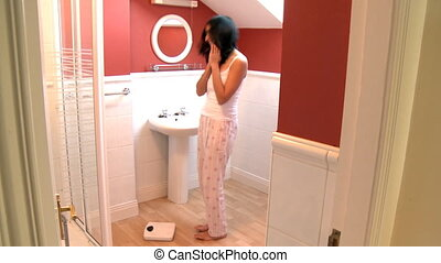 Blissful woman checking her weight in the bathroom