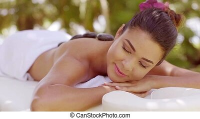Blissful young woman having a hot stone massage as she lies...
