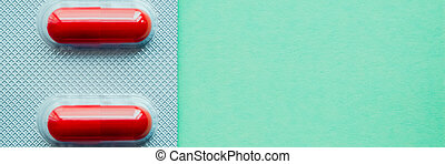 Blister bright red tablets on a green background.
