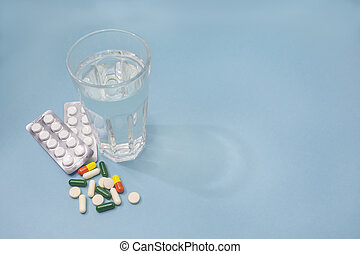 Blister with white pills, transparent glass of water and various pills and capsules are scattered on blue background. Copy space, selective focus. Pharmacology concept, health care