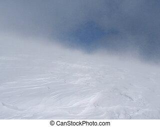 A snowstorm high into winter mountains