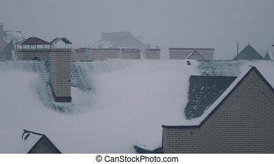 Blizzard above sloped roofs of residential houses in winter