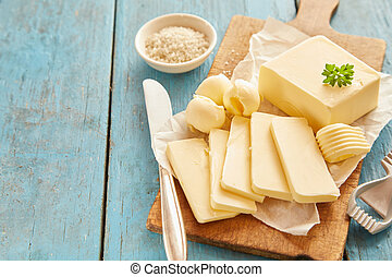 Block of butter sliced on wooden cutting board - Block of...