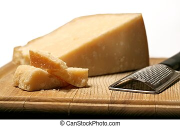 Block of parmesan cheese with metal grater on wooden cutting board