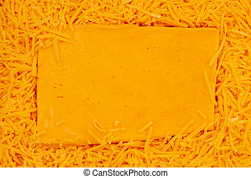Block of cheese on shredded cheddar cheese background