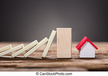 Block Stopping Domino Pieces Representing Home Insurance