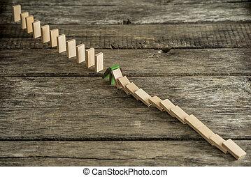 Blocking domino effect concept - Unpainted wooden domino...