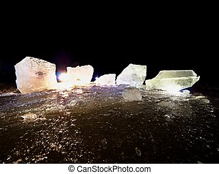 Blocks of shining ice and snow on the shore. The floes and crushed ice