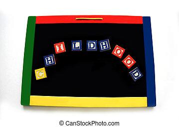 Blocks Spell Childhood on a Black Magnetic Board