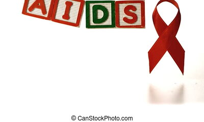 Blocks spelling Aids dropping down in front of a red ribbon...