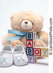 Blocks spelling baby boy with teddy and baby shoes on white...