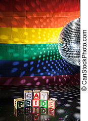 Blocks spelling out gay pride under light of disco ball with...