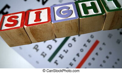 Blocks spelling out sight falling on eye test in slow motion...