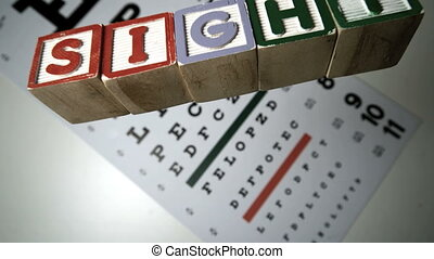 Blocks spelling sight falling on eye test in slow motion