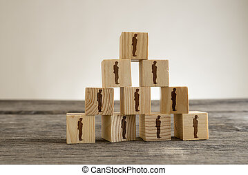 Blocks with businessman silhouettes structured into a pyramid
