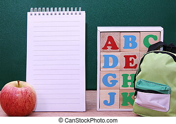 Blocks with letters of the English alphabet and a notebook next to them. Back to school.