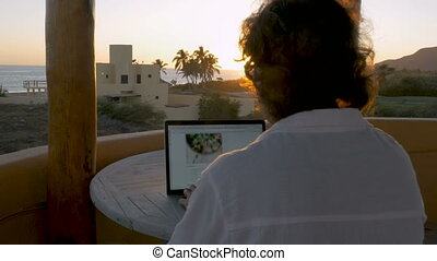 Blogger or graphic designer man working on laptop at home...