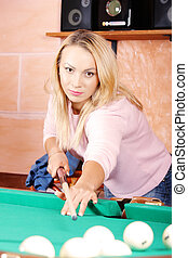 Blond aiming ball on billiards