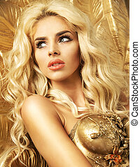 Blond alluring woman among the gold