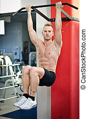 Blond, attractive young man hanging from gym equipment
