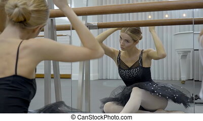 Blond ballerina sits in front of mirror and creates hairstyle for dance.