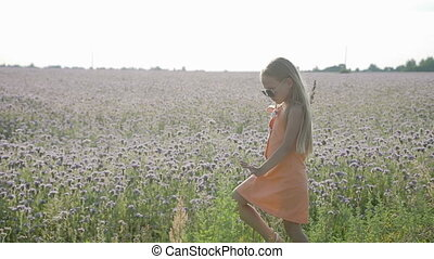 Blond, beautiful girl running in sunglasses on the background of wild flowers. Summer, hot and warm