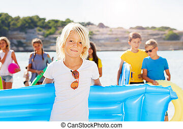 Blond boy on the beach with friends