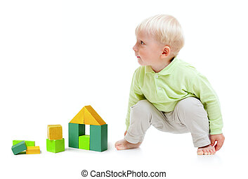 Blond boy playing at floor with building blocks isolated on white