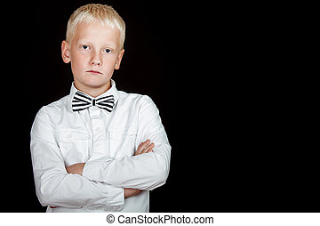 blond boy with bad attitude stares at camera with arms crossed against a black background