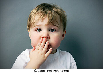 oops! cute and funny little blond boy or toddler with hand in front of mouth