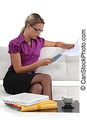 Blond businesswoman sat on a sofa reading through document