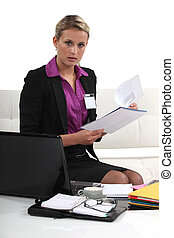 Blond businesswoman sat with report