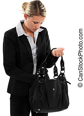 Blond businesswoman searching through her bag