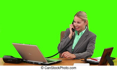 Blond businesswoman talking on the phone at her desk
