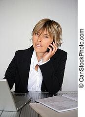 Blond businesswoman working away at her desk