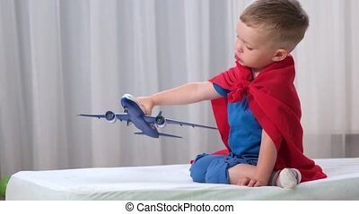 Blond caucasian boy super hero kid is playing with toy air plane in children's room dressed in red raincoat and blue t-shirt. Boy dreams of becoming an air pilot of an airplane.