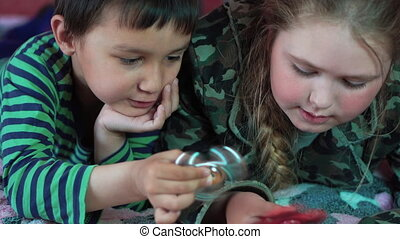 Blond Caucasian girl and a multi-ethnic boy playing at home with a Spinner toy 4K