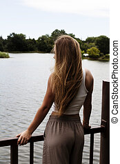 Blond Caucasian Teen Girl Standing At Rail Looking At River