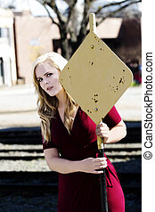 Blond Caucasian Woman In Red Dress Holding On To Yellow Sign
