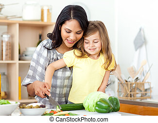 Blond child cutting vegetables with her mother