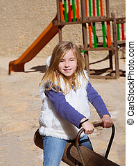 Blond child girl playing in playground smiling on swing