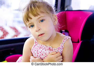blond child girl sitting in car safety seat