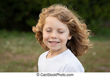Blond child laughing while imagines something in a park