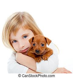 Blond children girl with dog puppy mascot mini pinscher on white background