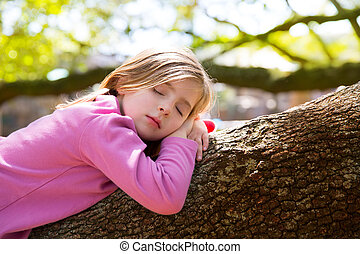 Blond children kid girl having a nap lying on a tree