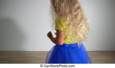 blond curly hair girl dancing in room. Playful child move her ass. Gimbal motion