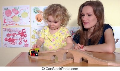 Blond cute girl and her mother play with toy train and clap hands