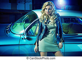 Blond elegant woman with the retro car in the background